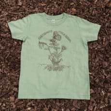 Light green men's t-shirt with butterfly logo on top of mulch