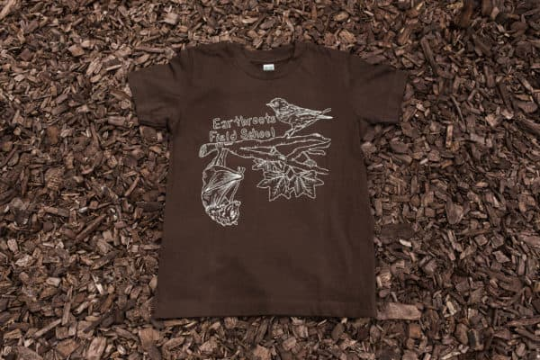 Brown men's t-shirt with bird and bat design on top of mulch