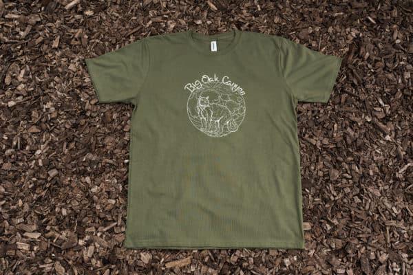 Dark green men's t-shirt with mountain lion design on top of mulch