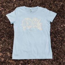 Light blue women's t-shirt with owl and oak design on top of mulch